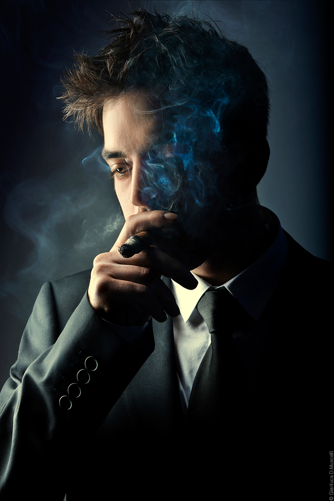 Young handsome stylish man smoking cigar